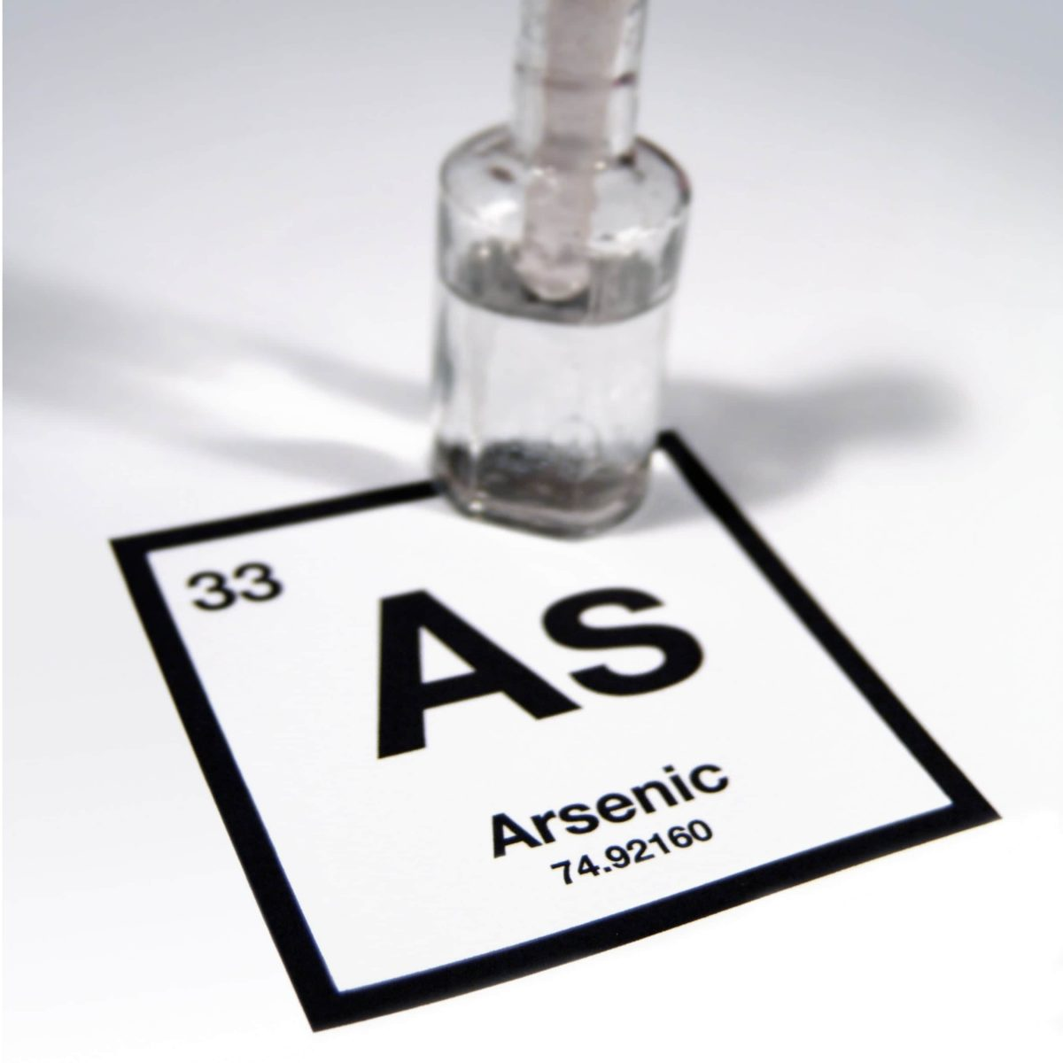 A clear bottle filled with liquid, sitting on a printed element of arsenic from the periodic table.